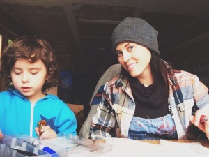 Phoebe Carpenter Eels and one of her sons working in her studio, and a few of her t-shirt designs (below). COURTESY PHOTO