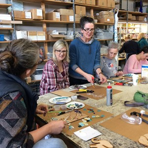 Debbie Dickinson (center, standing) talks with students at her Feb. 17 mosaic class, held at her studio on State Street in Bellingham. Students choose from the colorful tile scraps (all from the RE Store) stacked on shelves. PHOTO BY MARY VERMILLION